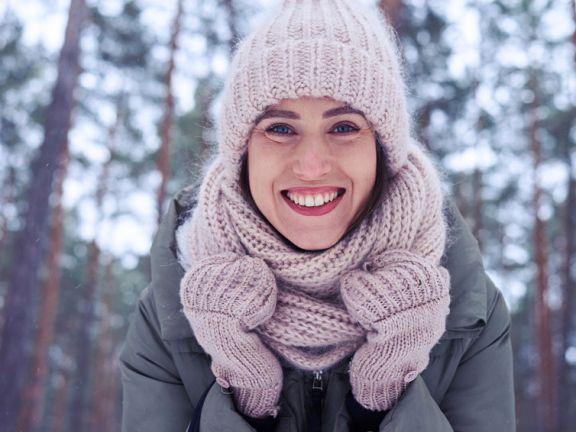 Junge Frau in Schal und Mütze lächelt vor winterlicher Landschaft in die Kamera