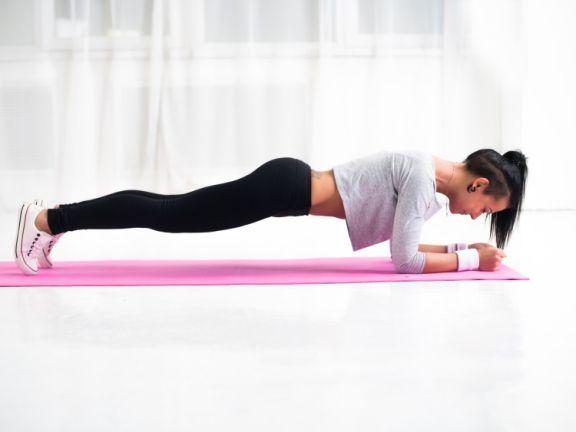 Trainierte junge Frau beim Planking auf einer Matte