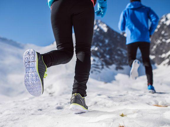 Zwei Menschen joggen im Schnee