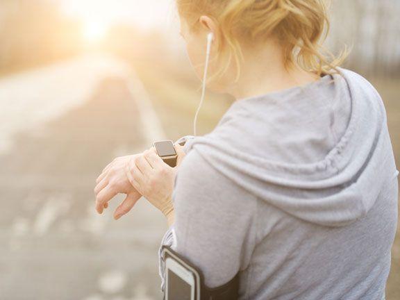 Frau schaut beim Joggen auf ihre Pulsuhr