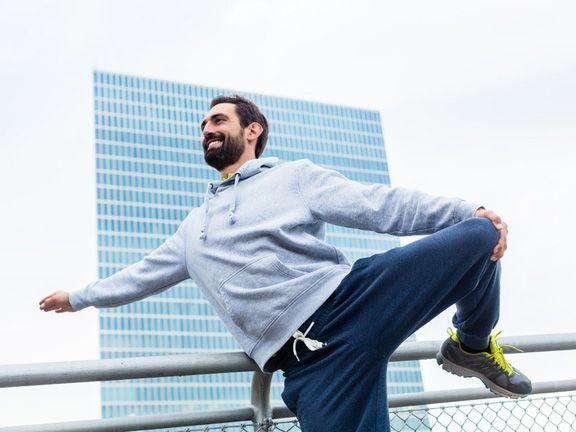 Mann macht Stretch-Übungen vor einem großen Hochhaus