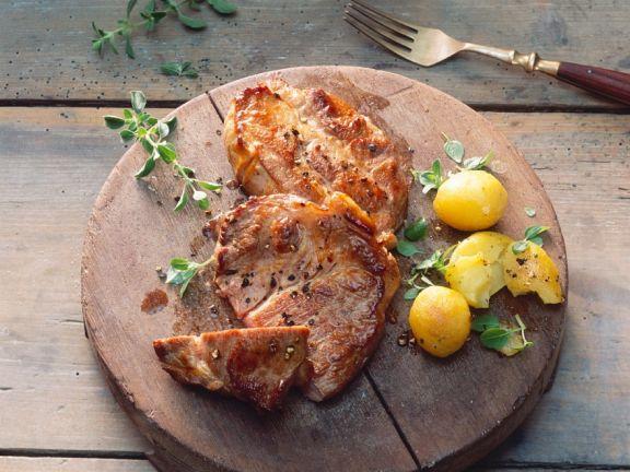 Gegrillte Schweinesteaks mit Kartoffeln