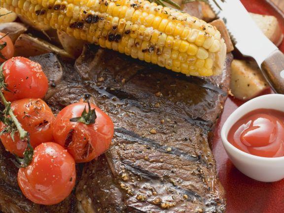 Gegrilltes Steak mit Maiskolben, Cherrytomaten, Kartoffeln und Ketchup