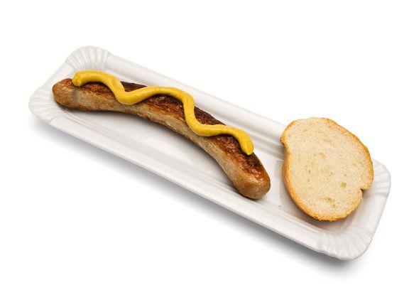 Grillwurst mit Senf und einem Stück Brot auf einer Pappe