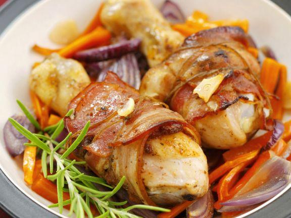 Hähnchenschlegel in Speckhülle auf Gemüse