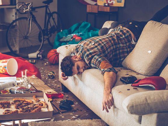 Verkaterter Mann liegt in einer chaotischen Wohnung auf der Couchlehne