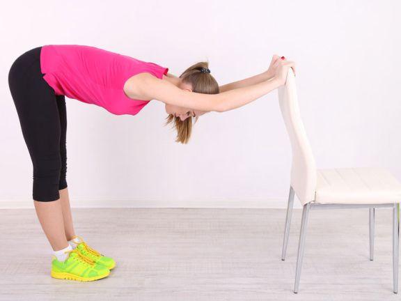 Frau stretcht ihren Rücken mit Hilfe eines Stuhls