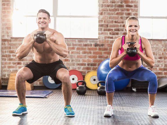 Muskulöses Paar trainiert mit Kettlebells