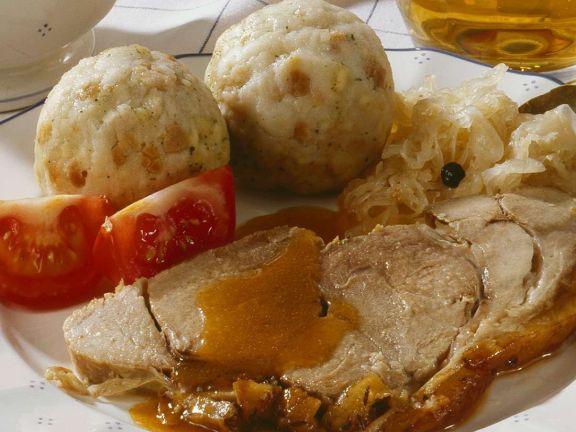 Klassischer Schweinebraten mit Klößen und Sauerkraut