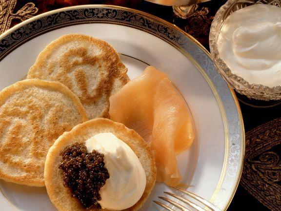 Kleine russische Pfannkuchen mit geräuchertem Lachs und Schmand