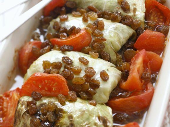 Kohlrouladen mit Fleisch gefüllt, dazu Tomaten und Sultaninen