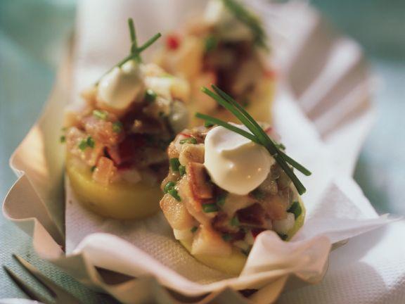 Matjeshäckerle auf geschnittenen Kartoffeln
