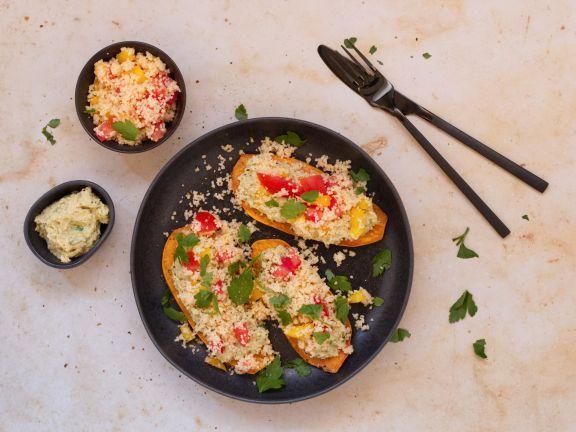 Süßkartoffeln auf einem schwarzen Teller belegt mit Hummus und Couscoussalat