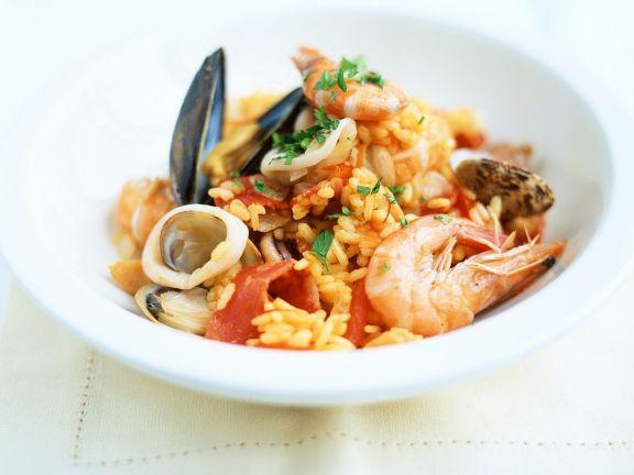 Paella mit Tintenfisch, Muscheln und Garnelen