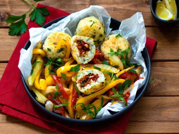 Paella-Reis-Bällchen gefüllt mit Tomaten auf mediterranem Gemüse