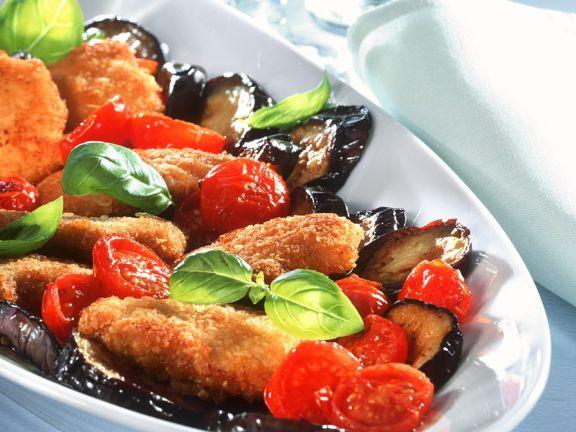 Panierte Schnitzelchen mit Auberginen und Tomaten