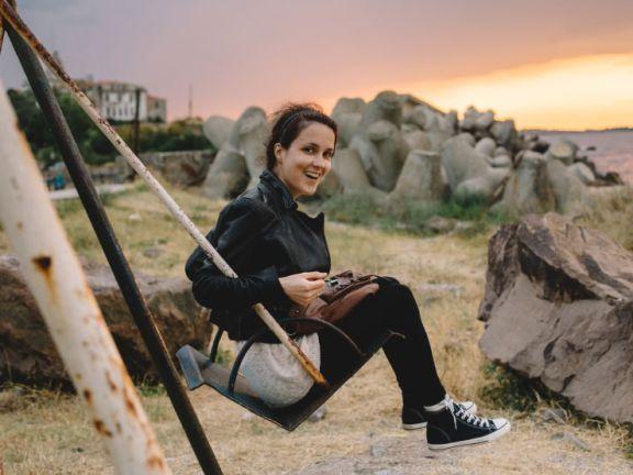 Junge Frau auf einer Schaukel vor dem Sonnenuntergang