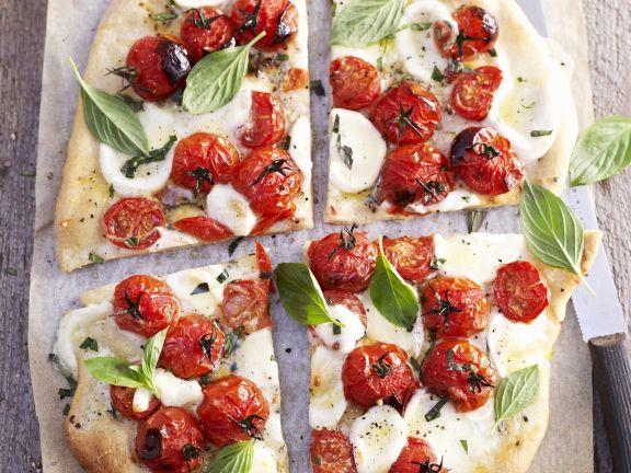 Pizza mit Tomaten, Mozzarella und Basilikum
