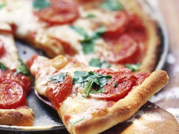 Pizza mit Tomaten und gebackenem Rucola