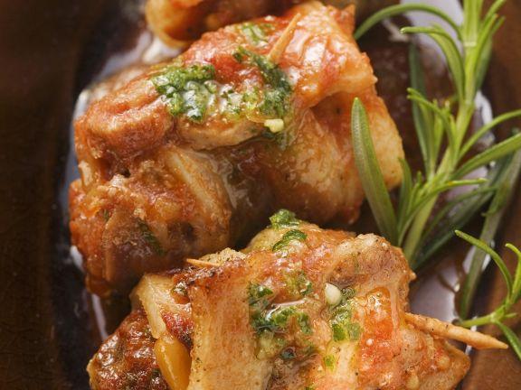 Röllchen vom Schweinebauch mit Tomatensugo und Kräuteröl