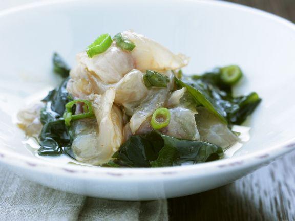 Roher Fisch mit Lauchzwiebeln und Algen