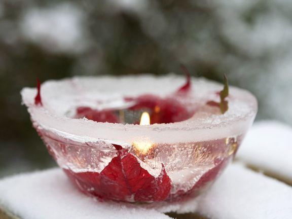 Schale aus Eis mit Weihnachtssternblüten und Kerze