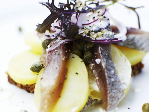 Schwarzbrot mit Belag aus Kartoffeln, Sardellen, Kapern und Zwiebeln