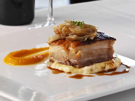 Schweinebauch mit Polenta, glasierten Schalotten und Möhrenpürree
