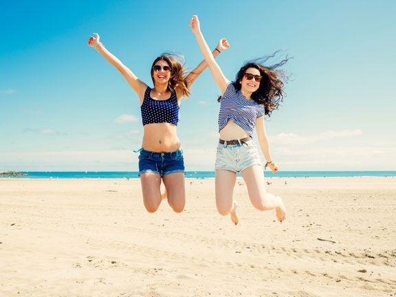 Zwei hübsche Frauen in Jeans-Shorts und schlanken Beinen springen fröhlich an einem Strand herum