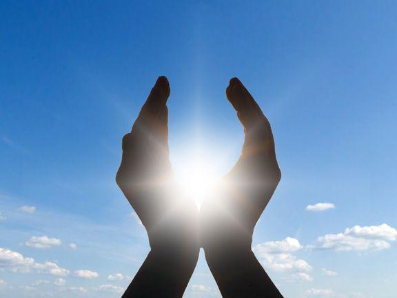Hände im Gegenlicht vor blauem Himmel