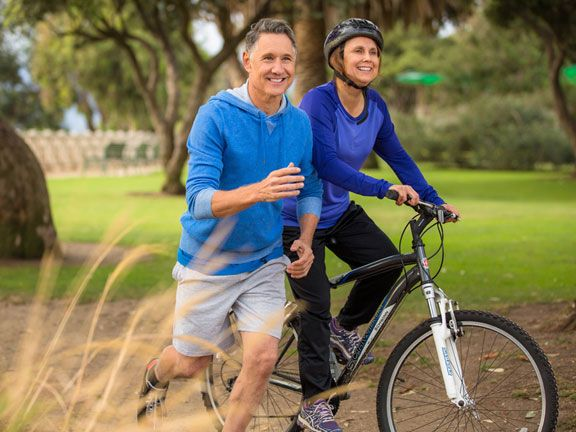 Älteres Paar joggt und fährt Rad im Park