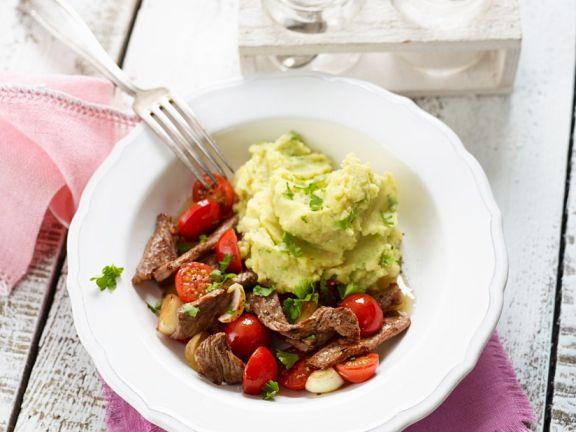 Steakstreifen mit Tomaten und Zwiebeln; dazu Kartoffel-Avocadopüree