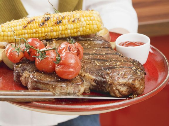 T-Bone-Steak mit gegrilltem Mais und Cherrytomaten