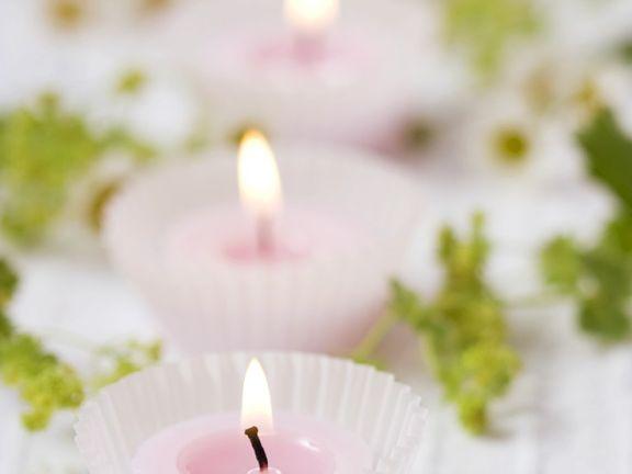 Teelichter in Muffinförmchen, Frauenmantel und Kamille