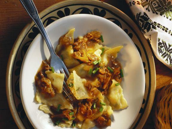Teigtaschen mit Schinken und Kartoffeln gefüllt, dazu Lammsoße