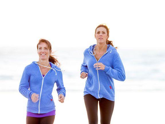 Zwei Frauen mit blauen Trainingsjacken joggen am Strand
