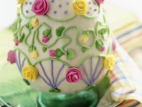 Torte in Ostereiform mit Rosen aus Zuckerguss dekoriert