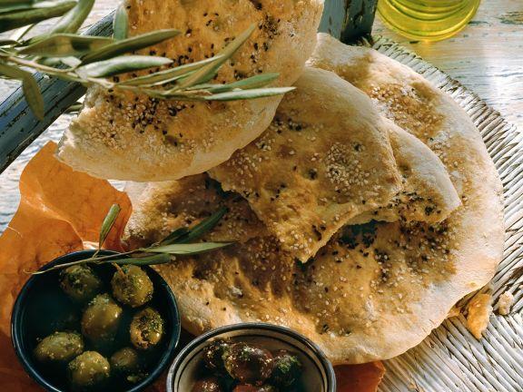 Türkisches Fladenbrot mit Sesam und Schwarzkümmel; Oliven