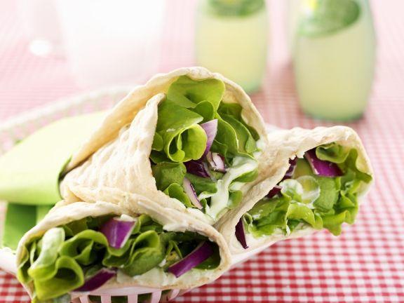 Vegetarische Wraps mit Wasabicreme, Avocado, Salat und roten Zwiebeln