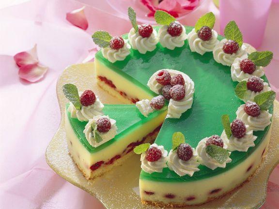 Waldmeister-Sekt-Torte mit Himbeeren und Sahnetupfen