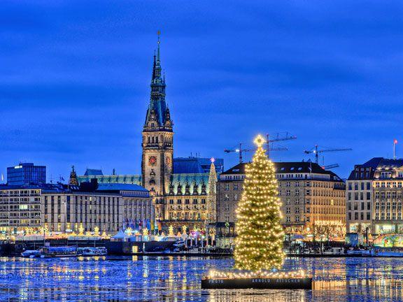 Hamburger Binnenalster weihnachtlich beleuchtet, im Hintergrund der Weihnachtsmarkt