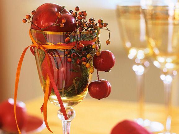Weinglas mit roten Äpfeln, Hagebutten und Moos gefüllt