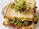Belegtes Brötchen mit Salami, Essiggürkchen und Sprossen Rezept